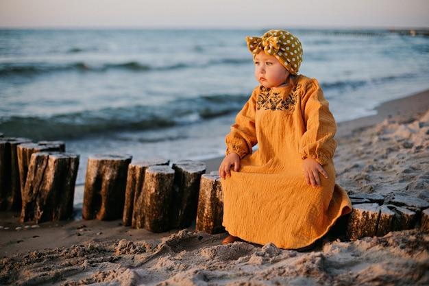 Klein meisje in oosterse kleding zittend op golfbreker op het strand van de oostzee