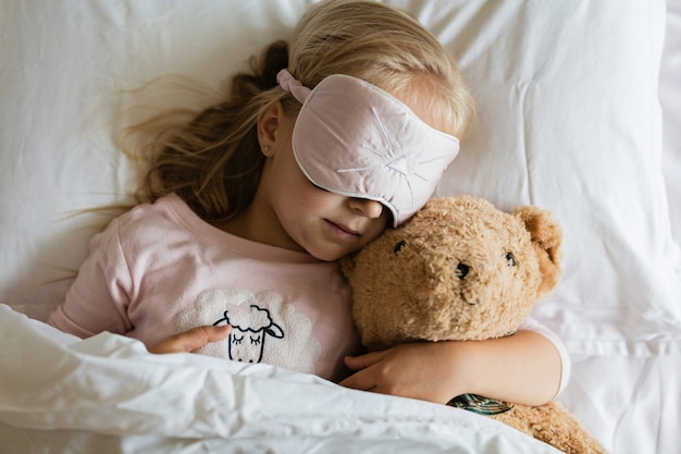 Klein meisje in pyjama en blinddoek slapen in witte bed met teddybeer