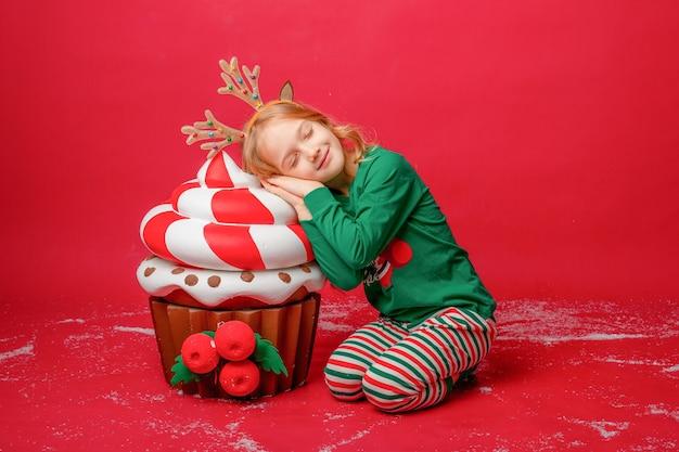 Klein meisje in pyjama op een rode achtergrond met geschenken