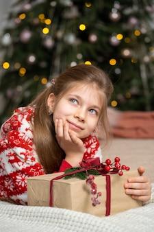 Klein meisje in pyjama 's morgens vroeg een cadeautje van de kerstman onder de boom gevonden
