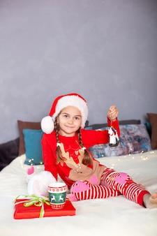 Klein meisje in rode pyjama's en kerstman hoed op bed