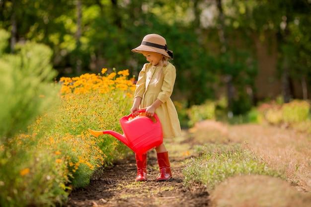 Klein meisje in rode rubberen bootswaterende bloemen in de tuin
