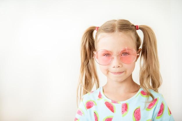 Klein meisje in roze bril, jeugdliefde. kind blij lief voelt sympathie. kind charmante glimlach verliefd. liefde symbool concept