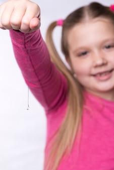 Klein meisje in roze houdt een uitgetrokken melktand vast aan een draad