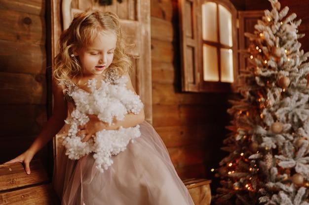 Klein meisje in roze jurk houdt nep sneeuw kersttijd vast