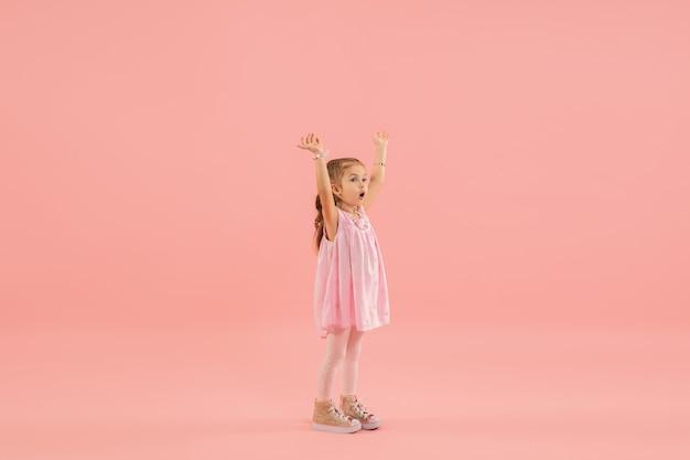 Klein meisje in roze jurk op roze muur