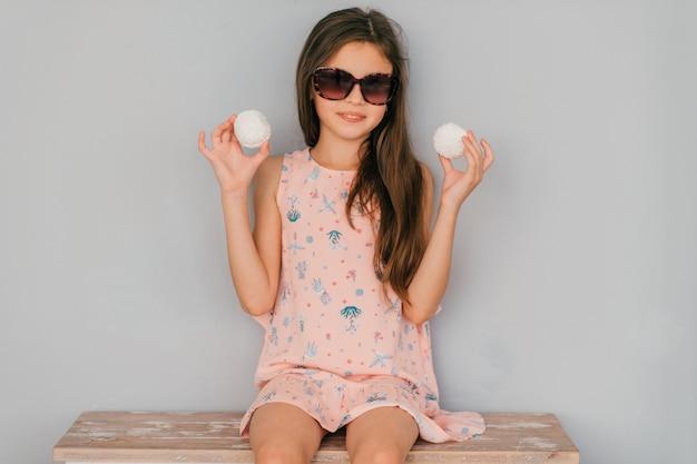 Klein meisje in roze jurk zitten in zonnebril met marshmallows in haar handen tegen grijze muur