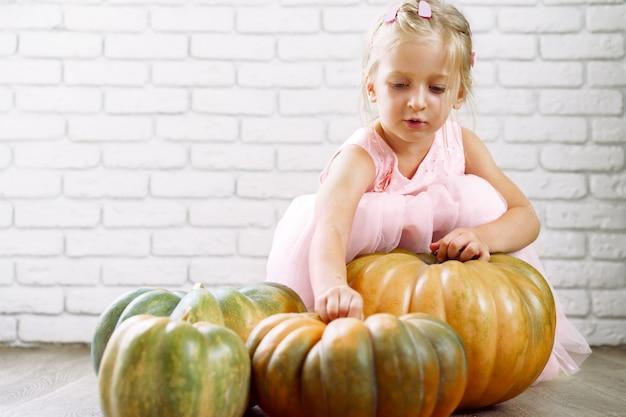 Klein meisje in roze jurk zittend op een houten vloer en spelen met stapel grote pompoenen