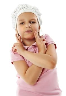 Klein meisje in roze shirt slaat een pose kijken naar de camera