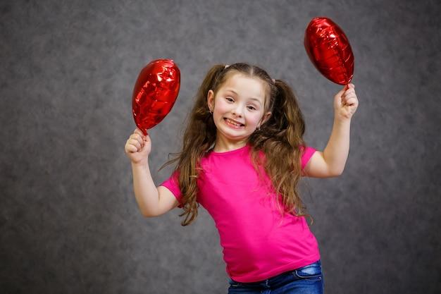 Klein meisje in roze t-shirt speelt met ballonnen
