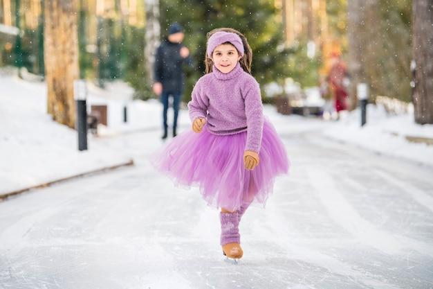 Klein meisje in roze trui en volledige rok rijdt op zonnige winterdag op een buitenijsbaan in park
