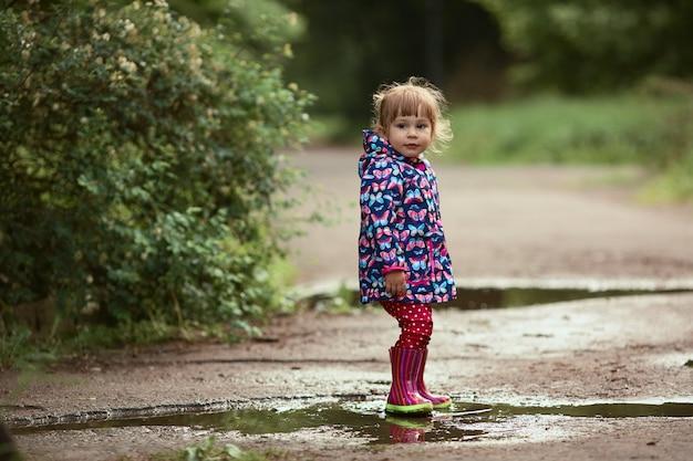Klein meisje in rubberlaarzen heeft plezier wandelen in de zwembaden na de regen