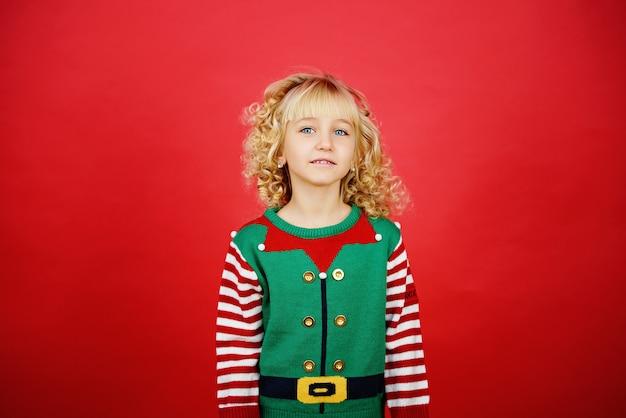 Klein meisje in santa elf helper kostuum op heldere rode levendige kleuren achtergrond.