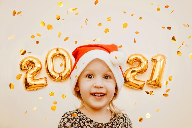 Klein meisje in santa glb glimlacht tegen de achtergrond van gouden getallen