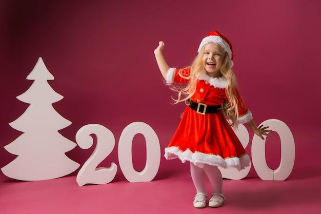 Klein meisje in santa kostuum staat met nummer 2020