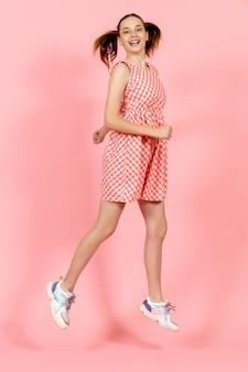 Klein meisje in schattige lichte jurk springen gelukkig op lichtroze