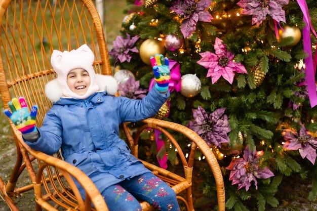 Klein meisje in schommelstoel bij kerstboom op straat
