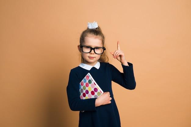 Klein meisje in schooluniform met boek over kleur achtergrond, bezit hand, hebben idee