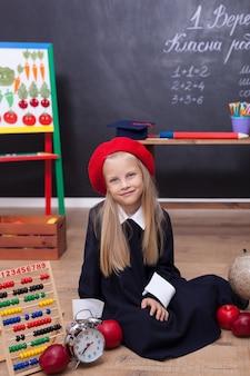 Klein meisje in schooluniform zit in les met een wekker, appels