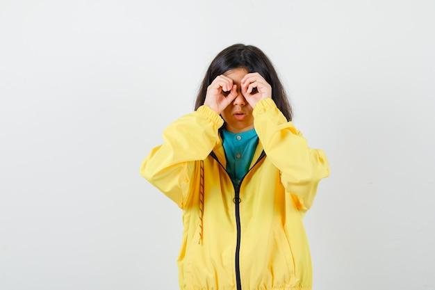 Klein meisje in shirt, jas die een brilgebaar toont en er grappig uitziet, vooraanzicht.