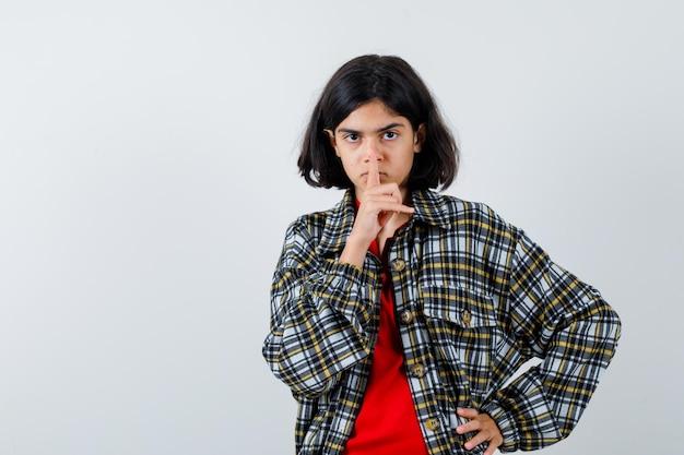 Klein meisje in shirt, jas die stiltegebaar toont en er serieus uitziet, vooraanzicht.