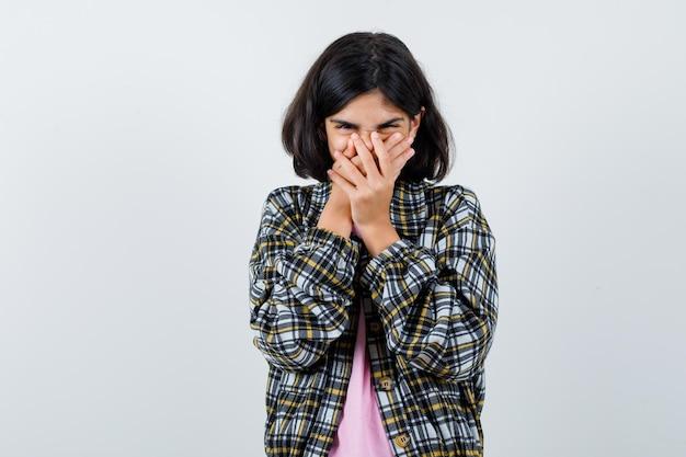 Klein meisje in shirt, jas hand in hand op mond terwijl ze lacht en vrolijk kijkt, vooraanzicht.