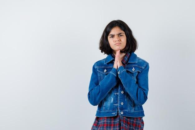 Klein meisje in shirt, jas houdt handen in gebedsgebaar en ziet er verdrietig uit, vooraanzicht.