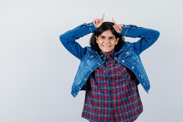 Klein meisje in shirt, jas houdt vingers boven het hoofd als stierenhoorns en ziet er grappig uit, vooraanzicht.