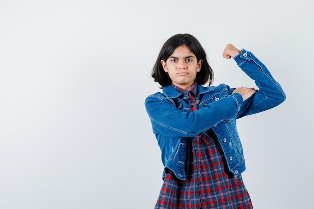 Klein meisje in shirt, jas met armspieren en zelfverzekerd, vooraanzicht.