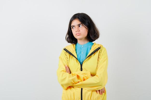 Klein meisje in shirt, jas met gekruiste armen terwijl ze wegkijkt en zelfverzekerd kijkt, vooraanzicht.