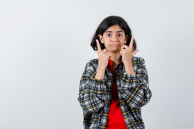 Klein meisje in shirt, jas naar boven gericht en zelfverzekerd, vooraanzicht.