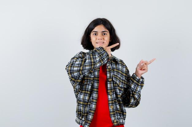 Klein meisje in shirt, jas opzij wijzend en vrolijk kijkend, vooraanzicht.
