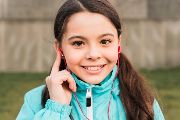 Klein meisje in sportkleding luisteren naar muziek
