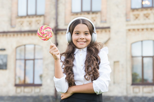 Klein meisje in stijlvol uniform eet lolly. terug naar school. modern onderwijs met nieuwe technologie. kind op schoolplein. stel je voor dat ze zangeres is. kind heeft muziekpauze. meisje in koptelefoon.