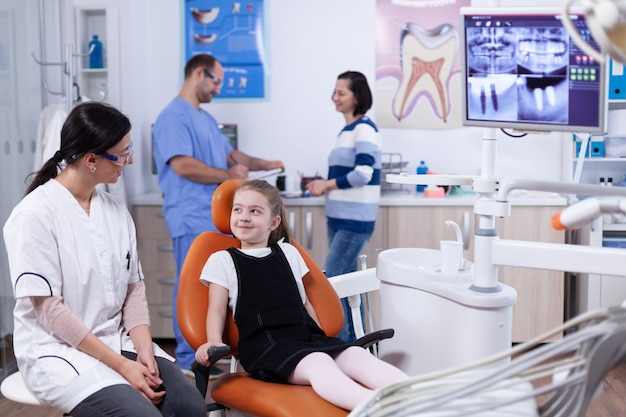 Klein meisje in stomatologie kantoor wachten op haar tanden medische procedure en onderzoek. kind met haar moeder tijdens tandencontrole met stomatolog zittend op een stoel.
