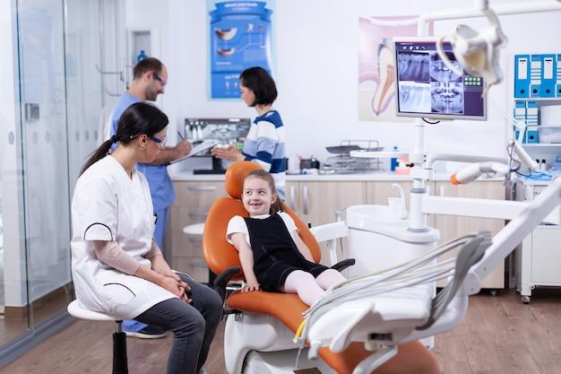 Klein meisje in stomatologiebureau voor tandenbehandeling die tandarts bekijkt. kind met haar moeder tijdens tandencontrole met stomatolog zittend op een stoel.