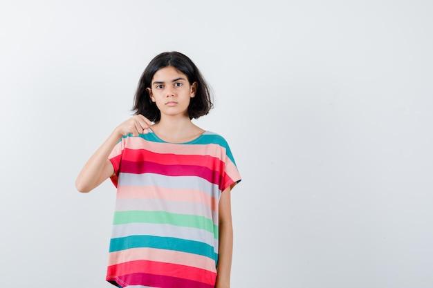 Klein meisje in t-shirt bedreigt met vuist en ziet er kalm uit, vooraanzicht.