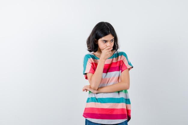 Klein meisje in t-shirt dat de hand op de kin houdt en er attent uitziet, vooraanzicht.