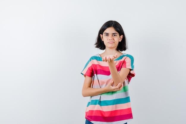 Klein meisje in t-shirt dat de hand uitrekt als iets vast te houden terwijl ze een hand op de elleboog houdt en er ontevreden uitziet, vooraanzicht.