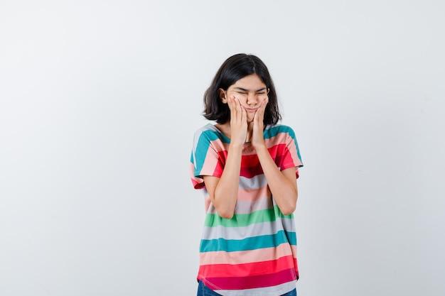 Klein meisje in t-shirt dat de handen op de wangen houdt en er boos uitziet, vooraanzicht.