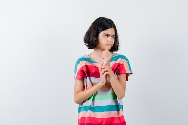 Klein meisje in t-shirt dat de vuist balt, hand op arm houdt, wegkijkt en ontevreden kijkt, vooraanzicht.