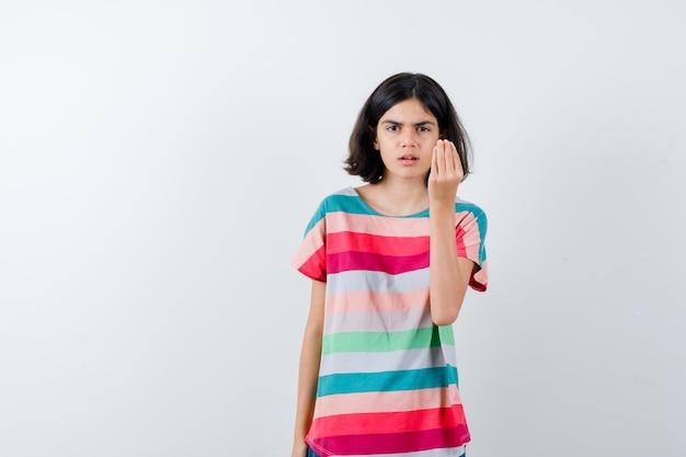 Klein meisje in t-shirt dat italiaans gebaar toont en er serieus uitziet, vooraanzicht.