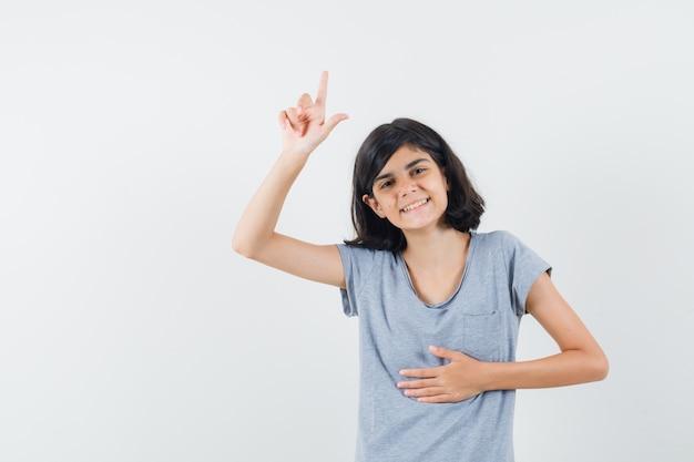 Klein meisje in t-shirt die omhoog wijst en gelukkig, vooraanzicht kijkt.