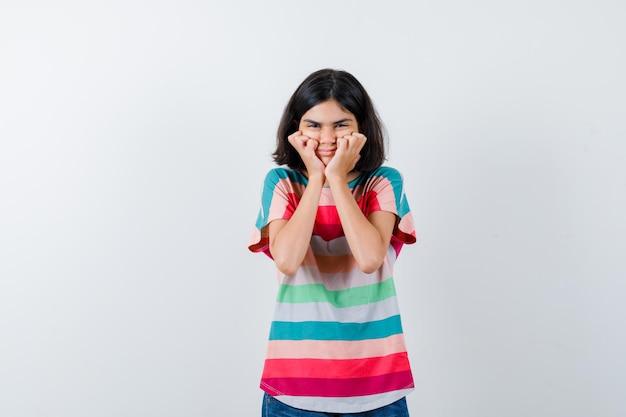 Klein meisje in t-shirt hand in hand op de wangen en ziet er gelukkig uit, vooraanzicht.