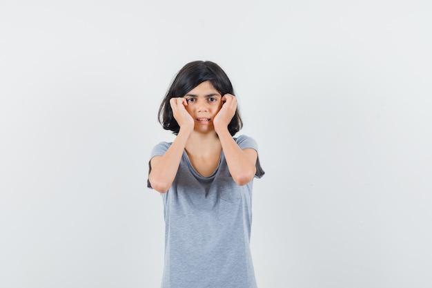 Klein meisje in t-shirt hand in hand op wangen en op zoek bang, vooraanzicht.