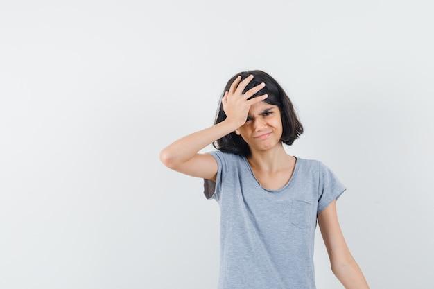 Klein meisje in t-shirt hand op het hoofd houden en spijtig, vooraanzicht op zoek.
