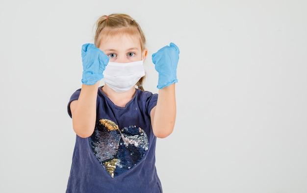 Klein meisje in t-shirt, handschoenen en masker verhogen handen met gebalde vuist en kijken vastberaden, vooraanzicht.