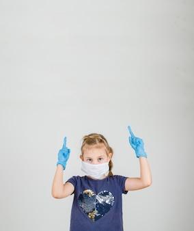 Klein meisje in t-shirt, handschoenen en masker wijzen vingers omhoog en op zoek voorzichtig, vooraanzicht.