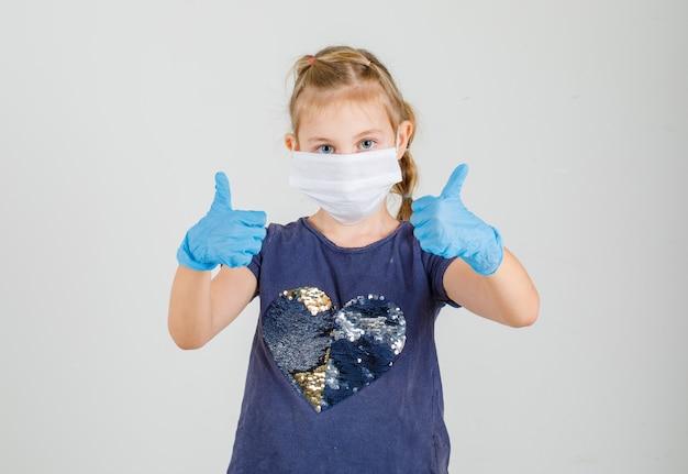 Klein meisje in t-shirt, handschoenen en medische masker maken duimen omhoog en op zoek naar vertrouwen, vooraanzicht.