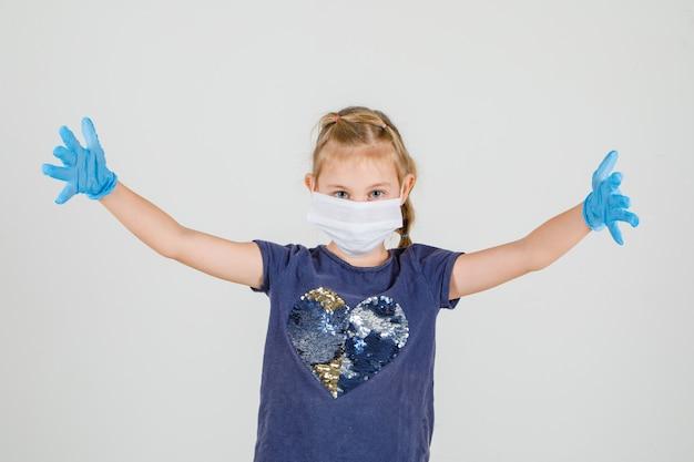 Klein meisje in t-shirt, handschoenen en medische masker verhogen haar handpalmen omhoog en op zoek gelukkig, vooraanzicht.